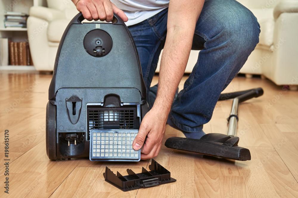 Fototapeta Replacing a hepa filter in vacuum cleaner at home.