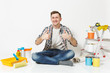 Man in casual clothes showing thumbs up, sitting on floor with instruments for renovation apartment isolated on white background. Wallpaper, gluing accessories, painting tools. Repair home concept.