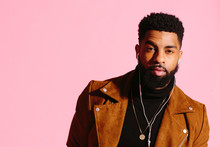 Cool Young African American Man With Beard Looking At Camera, Isolated On Pink Studio Background