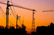 silhouette of building under construction with crane at sunset