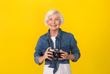 Senior Woman Traveler Studio Isolated On Yellow Wall Holding Camera Cheerful