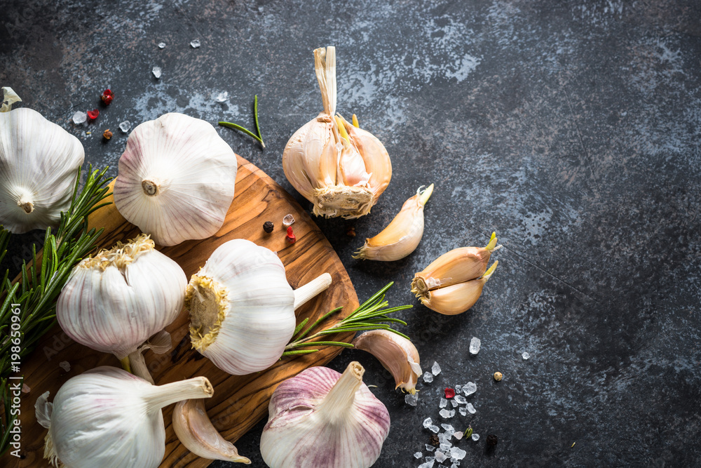 Garlic cloves with spices and herbs on a dark stone background.