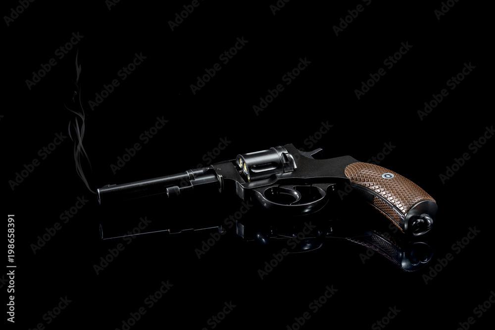 Fototapeta Revolver after a shot on a black background.