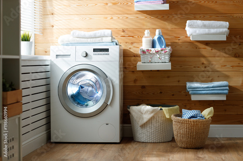 Fototapeta  Interior of real laundry room with  washing machine at window at home