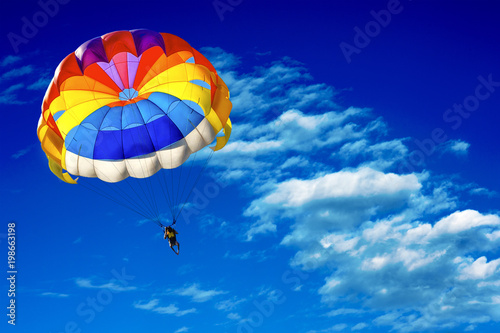 A man is gliding using a parachute on the background of cloudy blue sky Wallpaper Mural