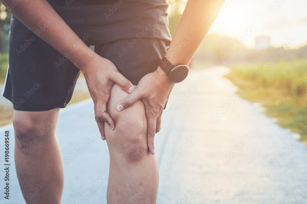 Fototapety, obrazy: Injury from workout concept : Asian man use hands hold on his knee while running on road in the park. Shot in morning time, sunlight and warm effect with copy space for text or design
