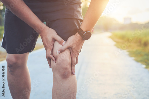 Fotografia  Injury from workout concept : Asian man use hands hold on his knee while running on road in the park
