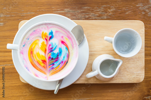 Colorful rainbow latte coffee in white cup on wooden table with copy space for t Poster Mural XXL