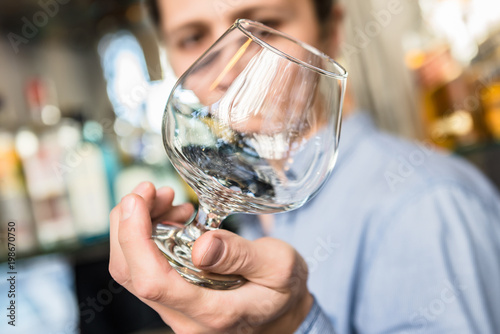 Barman Checking the Clarity of a Glass