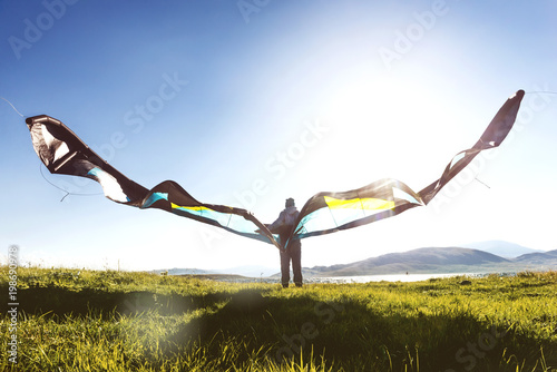 Photo sur Toile Aerien Man woman stands with kite in sun light