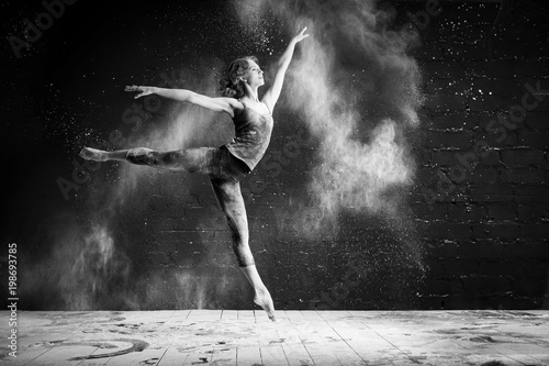 Fotografie, Obraz  beautiful ballet dancer dancing barefoot on black background in a cloud of dust