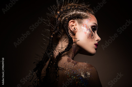 Fashion model with bright makeup and colorful glitter and sparkles on her face and body