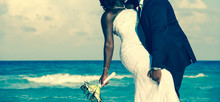 Passionate Afro-American Couple Kissing On Wedding Day By The Sea. Bride Holding Bouquet And Groom Grabbing Her Leg On The Beach. Ceremony Union, Valentine's Day, Love Concept.Vintage Effect