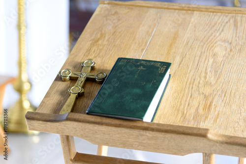 Golden cross crucifix with bible on wooden table. Christian church religion concept.