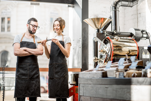Fotografija Couple of baristas in uniform checking the quality of roasted coffee beans stand