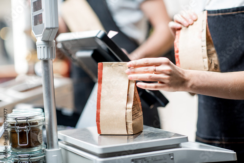 Weighing paper bag with coffee beans in the coffee store