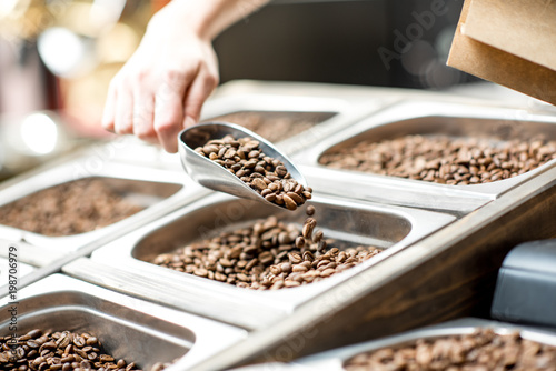 Fotografía  Filling paper bag with coffee beans from the metal trays for selling in the stor