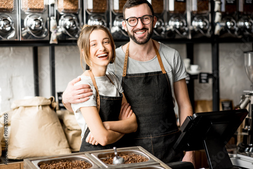 Fotomural Portrait of a young couple of baristas standing together at the counter of the c
