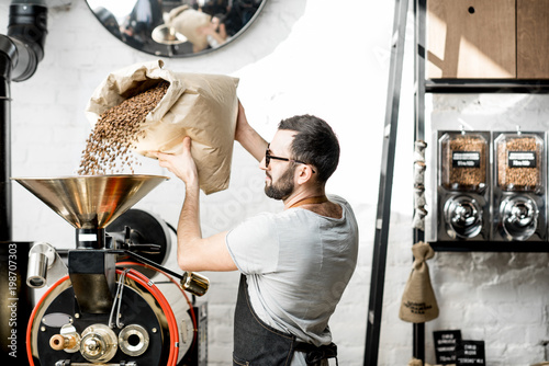 Fotografija Man pouring coffee beans into the roaster machine indoors