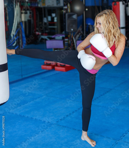 Young kickboxer woman kick into heavy bag in gym Canvas Print