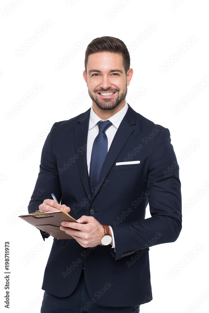 Fototapeta Young caucasian confident businessman writing on clipboard toothy smile isolated