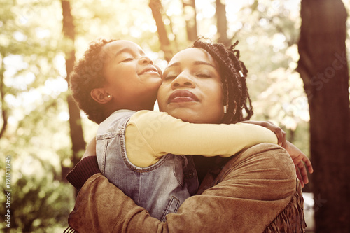 Fotografie, Tablou African American mother and her daughter hugging with daughter in forest