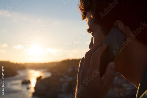Man calling with mobile phone watching sunset