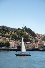 Sailboat Sailing Into Porto City On Douro River