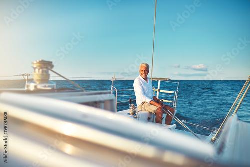 Fotografía  Smiling mature man sailing his yacht at sea