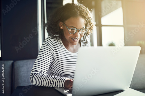 Smiling African woman working on her laptop at a table Wallpaper Mural