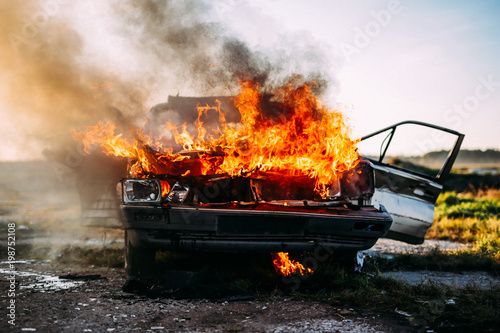 Canvastavla  Front of a car burning with a open flames  and dark smoke