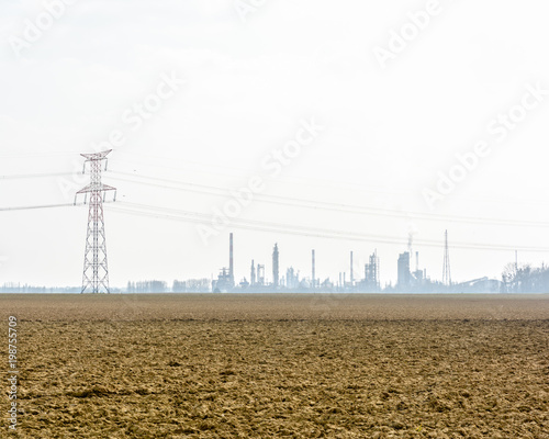 Fotografie, Obraz  View of a plowed land with a transmission tower, high-voltage power lines and the silhouettes of the smoking chimneys of a refinery on the horizon under a pale sunlight