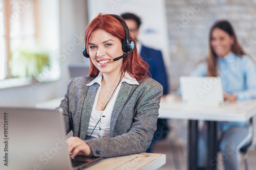 Fototapety, obrazy: Portrait of happy smiling female customer support phone operator at workplace.