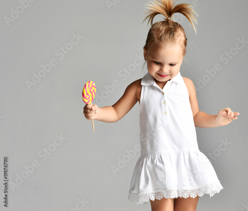 Fotografija  Young pretty toddler girl kid with big  sweet lollypop candy in white dress on g