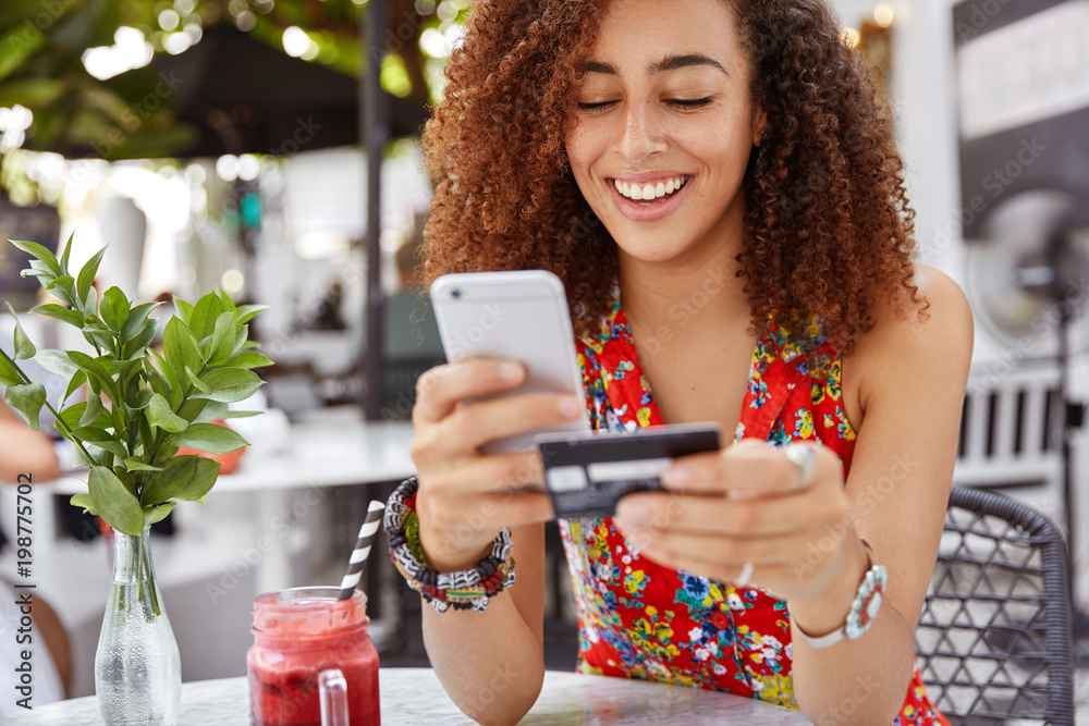 Fototapeta Beautiful dark skinned young female with cheerful expression, holds smart phone and credit card, banks online or makes shopping while sits against cafe interior. Payment and leisure concept.