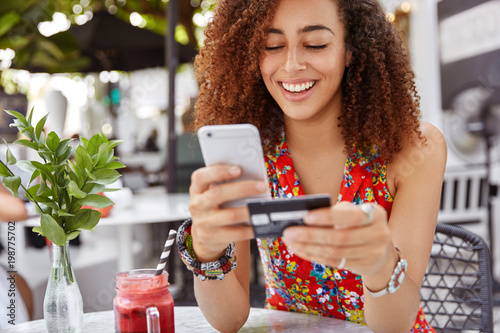 Carta da parati Beautiful dark skinned young female with cheerful expression, holds smart phone and credit card, banks online or makes shopping while sits against cafe interior