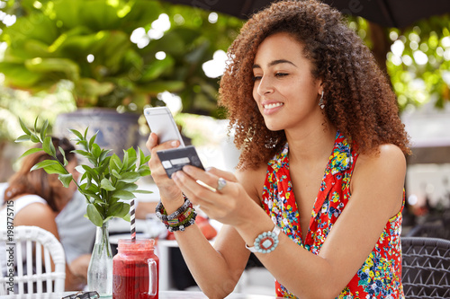 Fotografía  Shot of beautiful glad young female with Afro hairdo, types number of credit car