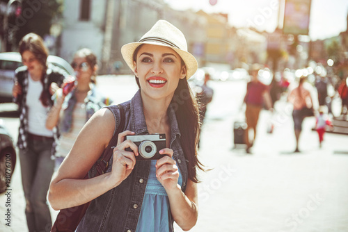 Fototapeta Portrait of pleased young woman doing images by camera while looking sightseeing. Glad tourist walking concept obraz