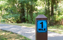 A One Mile Marker Sign Post Be...