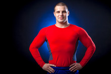 A Strong Dark-haired Sportman  In A Red Sports Wear  Rush Guard Posing Against A Blue A Lights On A Black Isolated  Background