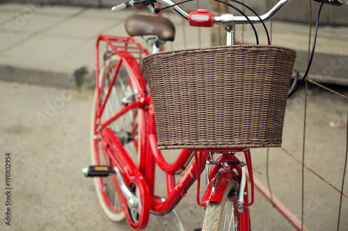 Velo Close-up view of the brown basket on the handlebar of the red vintage city bicycle outdoors. The concept of the healthy lifestyle, environment protection, green energy, convenient transport.