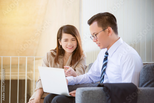 Foto  Young asian businesswoman talking about work with her partner in office