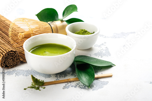 Green matcha tea drink and tea accessories on white background