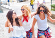 Three young female friends walking in city street laughing and having fun.