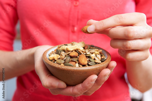 Fotografia, Obraz  Close Up Of Woman Eating Bowl Of Healthy Nuts And Seeds