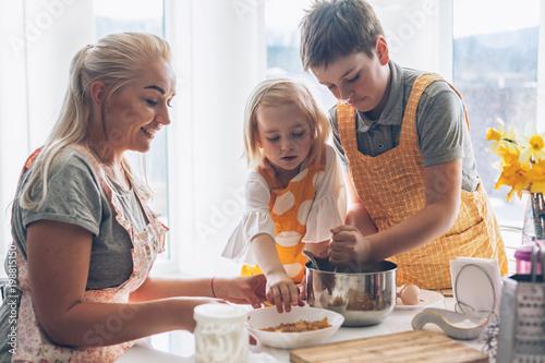 Foto op Plexiglas Koken Mom cooking with kids on the kitchen