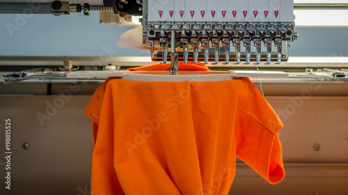 Cuadros en Lienzo Embroidery machine from the front, stiching a orange poloshirt