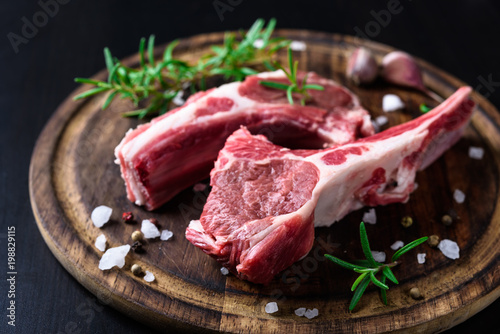 Fototapeta Two raw lamb chops on a wooden cutting board with spices on a dark wooden backgr