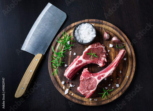 Photo  Two raw lamb chops on a wooden cutting board with spices on a dark wooden backgr