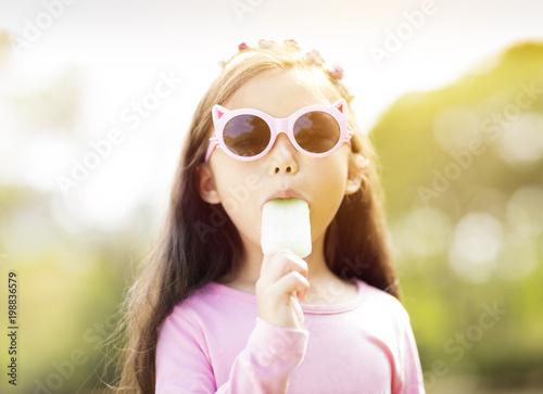 Foto  Glückliches kleines Mädchen, das Popsicle an der Sommerzeit isst.